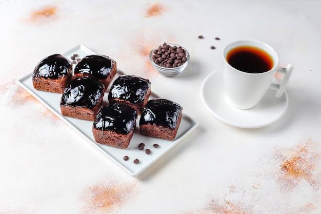 Kawałki ciasta czekoladowego z sosem czekoladowym i owocami.