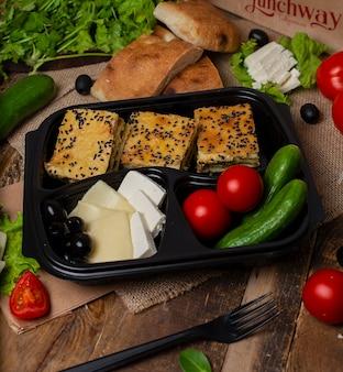 Kawałki ciasta mięsnego z warzywami, pomidorem, ogórkiem, oliwkami i serem