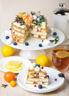 Kawałki ciasta miodowego na talerzu z herbatą cytrynową na deser.