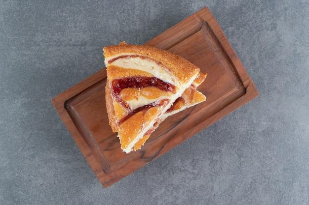 Kawałki ciasta owocowego na drewnianej desce do krojenia
