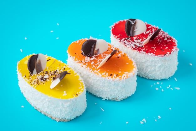 Kawałki ciasta ozdobione są płatkami kokosowymi. kolorowe ciasto na niebieskim tle. domowy pieczony kolorowy deser.