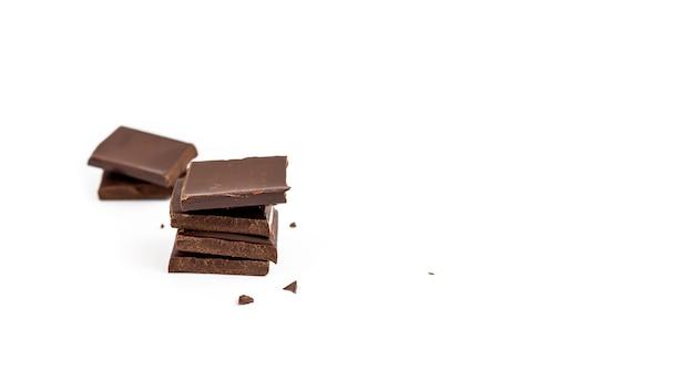 Kawałki ciemnej czekolady na białym tle na białej powierzchni, słodki deser