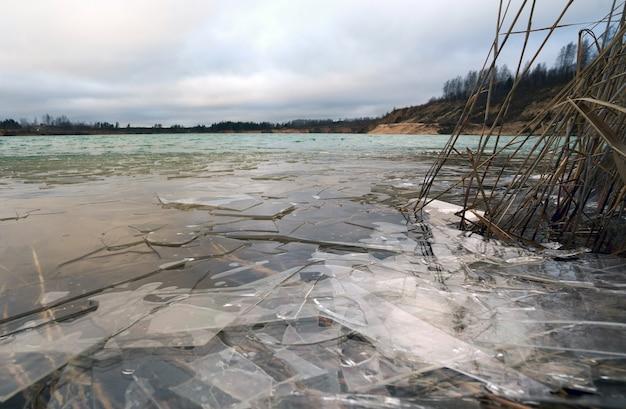 Kawałki cienkiego lodu na wodzie z kamieniołomu. obwód leningradzki.