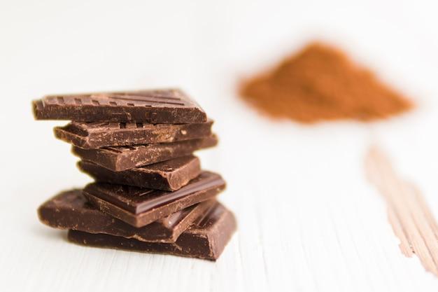 Kawałki czarnej czekolady i niewyraźne sterty proszku kakaowego
