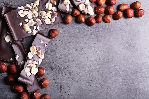 Kawałki czarnej czekolady i orzechy na ciemnoszarym