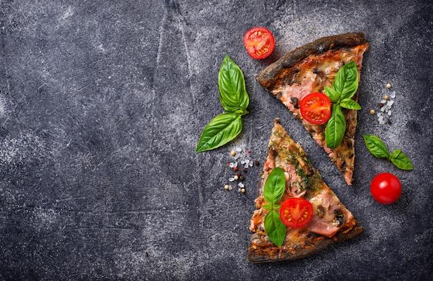 Kawałki czarnej pizzy z pomidorami i bazylią