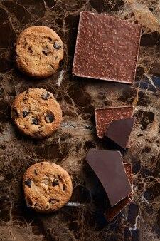 Kawałki czekolady i ciasteczka z czekoladą krople na ciemnym marmurowym tle