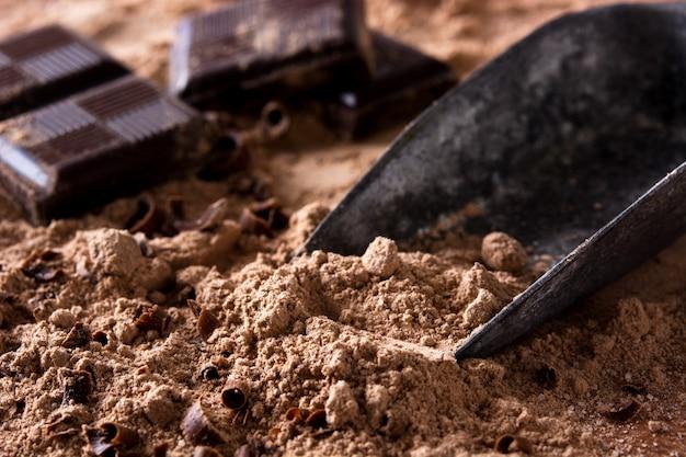 Kawałki czekolady i metalowa łyżka na proszku czekoladowym zamknij się
