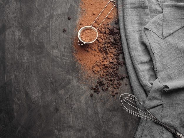Kawałki czekolady, kakao w proszku, trzepaczka do ciasta leży na szarym tle z szarą szmatką. skopiuj miejsce. widok z góry.