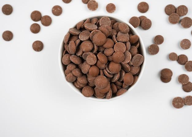 Kawałki czekolady mlecznej w białej misce na białym tle z miejsca na kopię