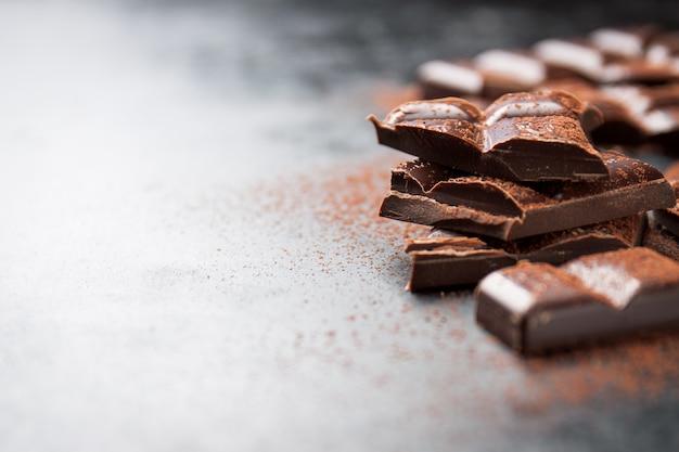 Kawałki czekolady na drewnianym stole i posypane kakao