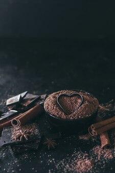 Kawałki czekolady z proszkiem kakaowym i sercem na ciemnym tle