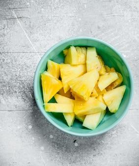 Kawałki dojrzałego ananasa w misce. na białym rustykalnym stole