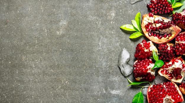 Kawałki dojrzałego granatu z liśćmi i lodem. na kamiennym stole. wolne miejsce na tekst. widok z góry