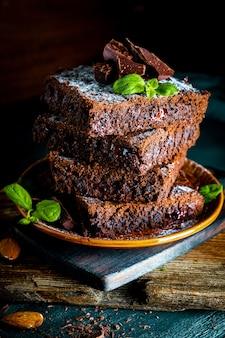 Kawałki domowego ciasta czekoladowego przyozdobione listkami mięty, zdjęcie pionowe. wysokiej jakości zdjęcie