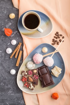 Kawałki domowej czekolady z cukierkami kokosowymi i filiżanką kawy na czarnej betonowej powierzchni. widok z góry, z bliska.