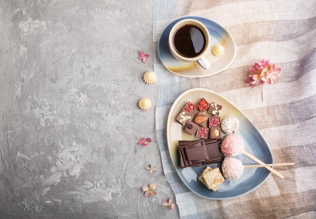 Kawałki domowej czekolady z cukierkami kokosowymi i filiżanką kawy. widok z góry