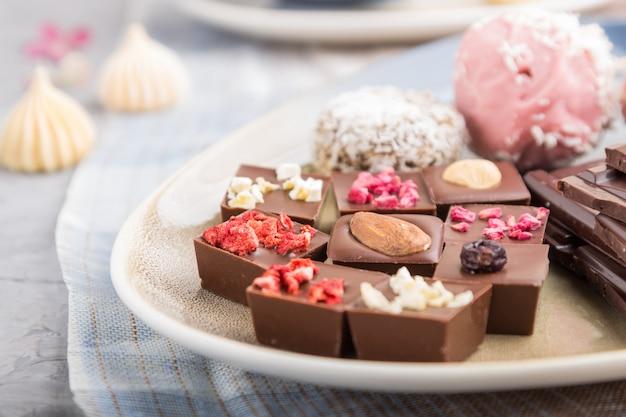 Kawałki domowej czekolady z cukierkami kokosowymi na niebiesko-brązowej tkaninie. widok z boku, selektywne focus.