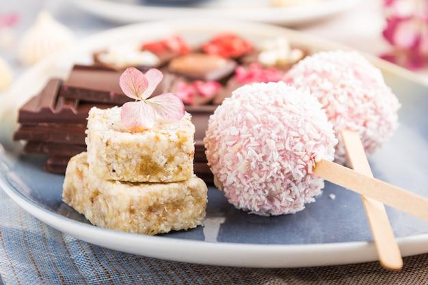 Kawałki domowej czekolady z cukierkami kokosowymi na niebiesko-brązowej tkaninie. widok z boku