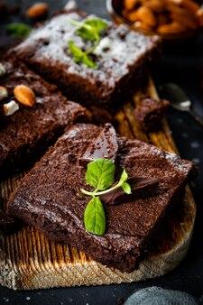 Kawałki domowej roboty brownie czekoladowe przyozdobione liśćmi mięty z bliska pionowe zdjęcie. wysokiej jakości zdjęcie