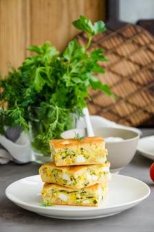 Kawałki domowej roboty ciasto z jajkami, zieloną cebulą i konserwowanym tuńczykiem na białym talerzu na ciemnym betonowym tle. orientacja pionowa.