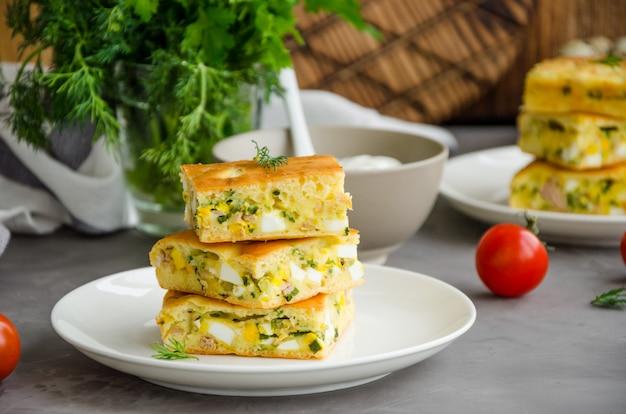 Kawałki domowej roboty ciasto z jajkami, zieloną cebulą i konserwowanym tuńczykiem na białym talerzu na ciemnym betonowym tle. orientacja pozioma.