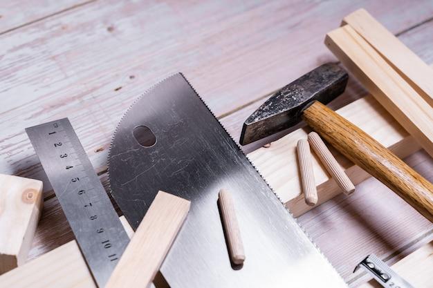 Kawałki drewna i narzędzia do budowy i naprawy na drewnianym stole