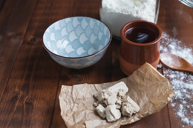 Kawałki drożdży na papierze z pojemnikami i składnikami na drewnianym podłożu do robienia zakwasu. koncepcja piekarni.