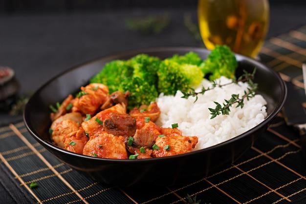 Kawałki fileta z kurczaka z pieczarkami duszone w sosie pomidorowym z gotowanymi brokułami i ryżem. odpowiednie odżywianie. zdrowy tryb życia. menu dietetyczne.