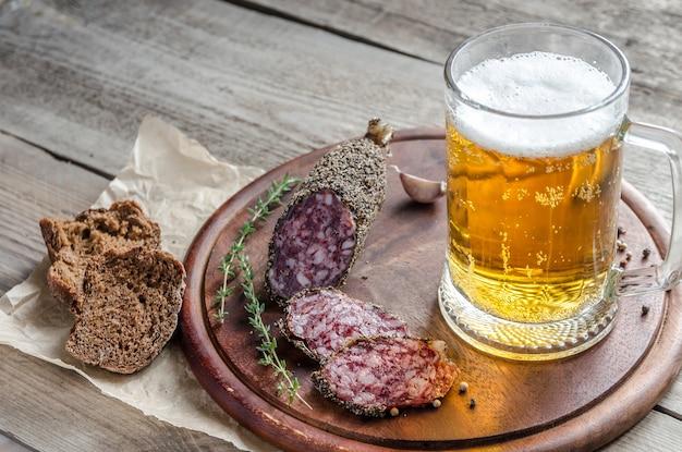 Kawałki francuskiej kiełbasy saucisson ze szklanką piwa