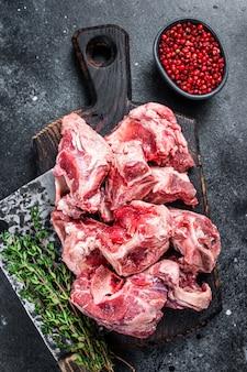 Kawałki gulasz surowego mięsa jagnięcego z kością na drewnianej desce rzeźniczej i tasaku. czarne tło. widok z góry.