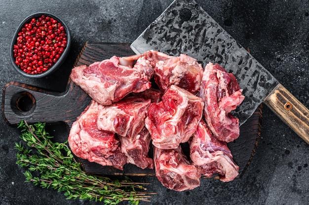Kawałki gulaszu surowego mięsa jagnięcego z kością na drewnianej desce rzeźnika i tasaku. czarne tło. widok z góry.