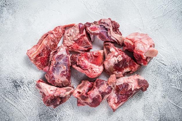 Kawałki gulaszu z surowego mięsa jagnięcego z kością. białe tło. widok z góry.