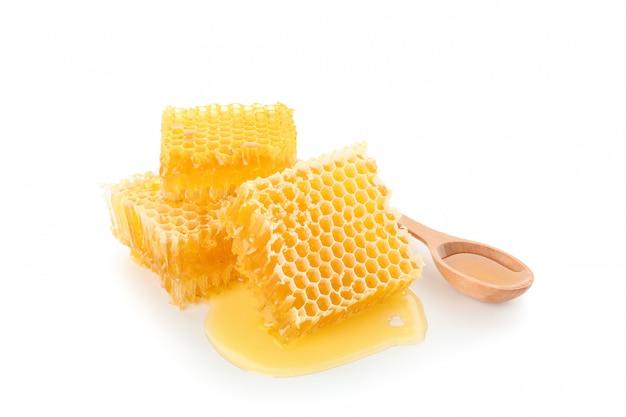 Kawałki honeycomb i drewniana łyżka odizolowywający na białym tle