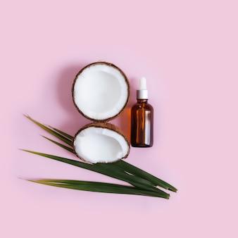 Kawałki i połówki kokosa i zielonych liści palmowych, szklana butelka z olejkiem eterycznym na pastelowym różowym tle.