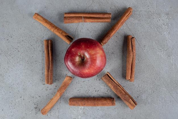 Kawałki jabłka i cynamonu ozdobnie ułożone na marmurowej powierzchni