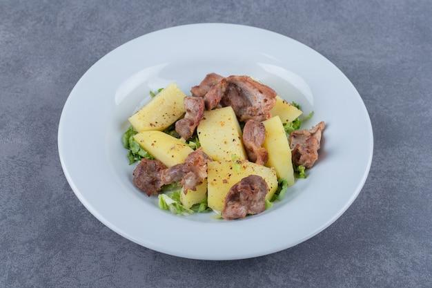 Kawałki kebaba i gotowane ziemniaki na białym talerzu.