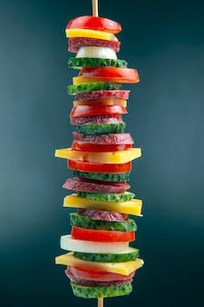 Kawałki kiełbasy, salami, ser, ogórek, pomidor w plasterkach. fast food. składniki na pizzę. kalorie i dieta