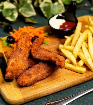 Kawałki kurczaka w stylu kfc z frytkami, majonezem, keczupem i sałatką warzywną
