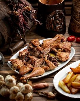 Kawałki kurczaka z grilla i serwer z frytkami ziemniaczanymi.