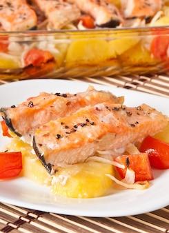 Kawałki łososia z ziemniakami, pomidorami i cebulą zapiekane w piekarniku