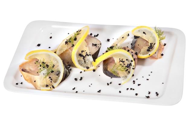 Kawałki makreli wędzone na zimno ozdobione plasterkami cytryny na prostokątnym białym talerzu ceramicznym, na białym tle.