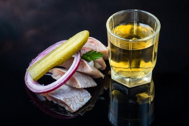 Kawałki marynowanego śledzia z ogórkiem i cebulą oraz narodowy napój jenever.