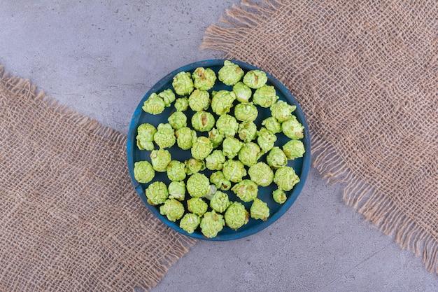 Kawałki materiału ułożone pod małą tacą z porcją zielonego popcornu na marmurowym tle. zdjęcie wysokiej jakości