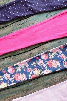 Kawałki materiału z nadrukiem. kolorowe tkaniny na drewnianym tle. odzież na zamówienie w uczciwej cenie. wysokiej jakości materiały w magazynie.