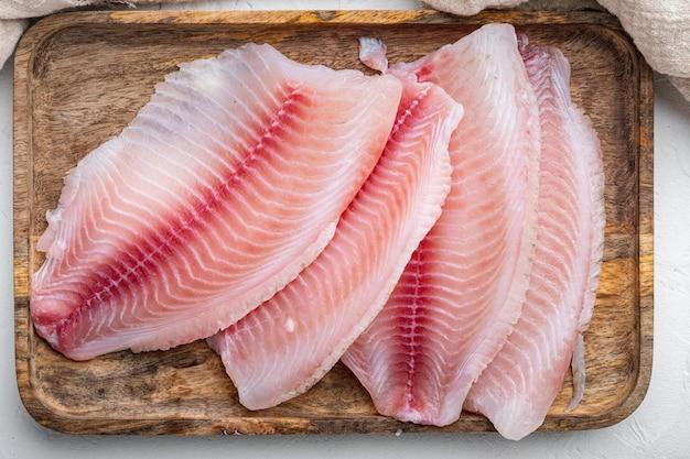 Kawałki mięsa surowego fileta rybnego tilapia, na białym tle, widok z góry