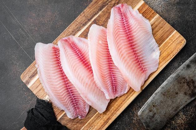 Kawałki mięsa surowego fileta rybnego tilapia, na starym rustykalnym tle, widok z góry