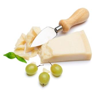 Kawałki parmezanu i nóż na białym stole