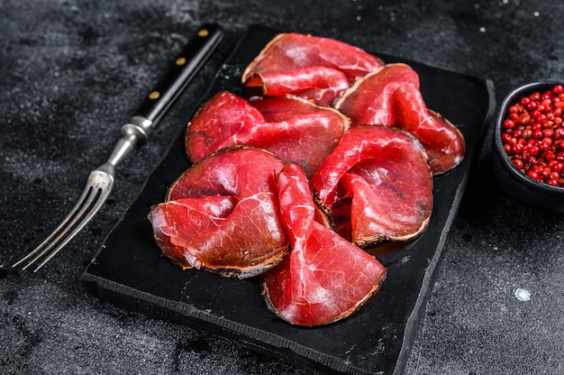 Kawałki peklowanej wołowiny bresaola, włoskie antipasti. czarne tło. widok z góry.