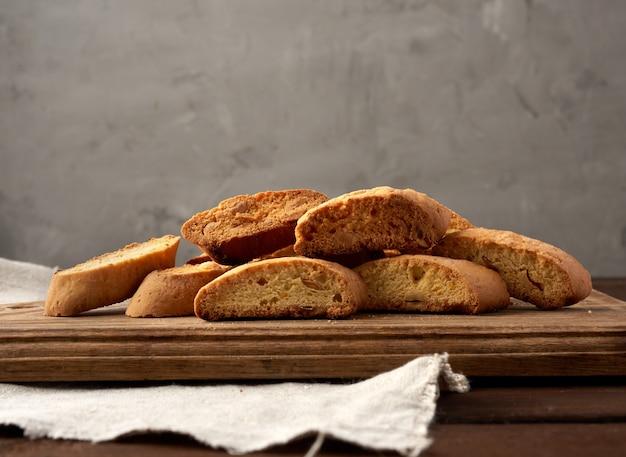 Kawałki pieczonych włoskich ciastek biscotti na brązowej desce